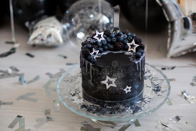 Black cake with stars and berries. With the number one royalty free stock photo
