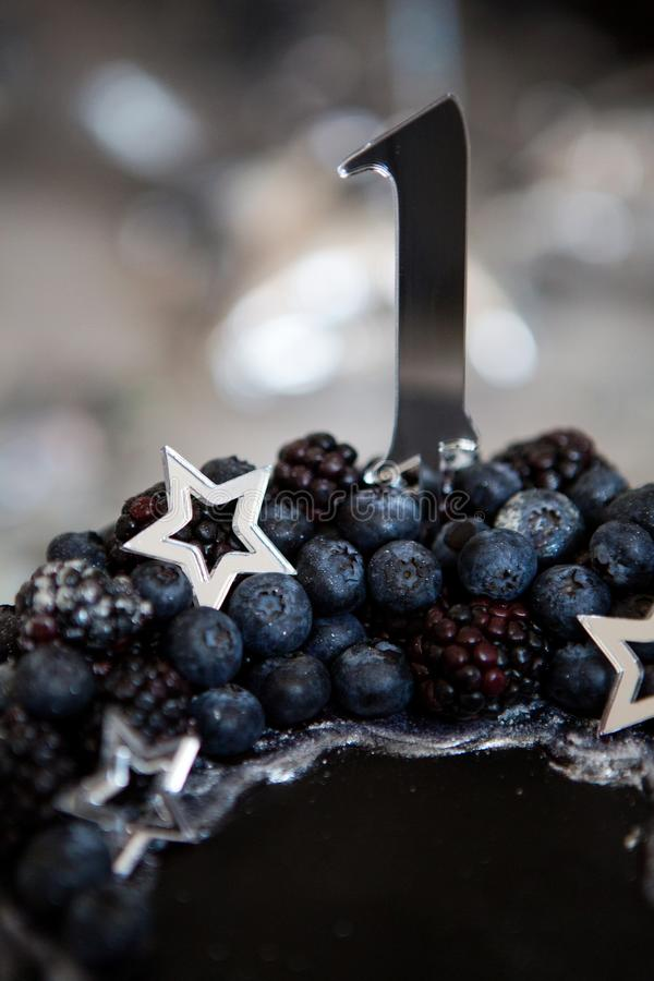Black cake with stars and berries. With the number one royalty free stock photos