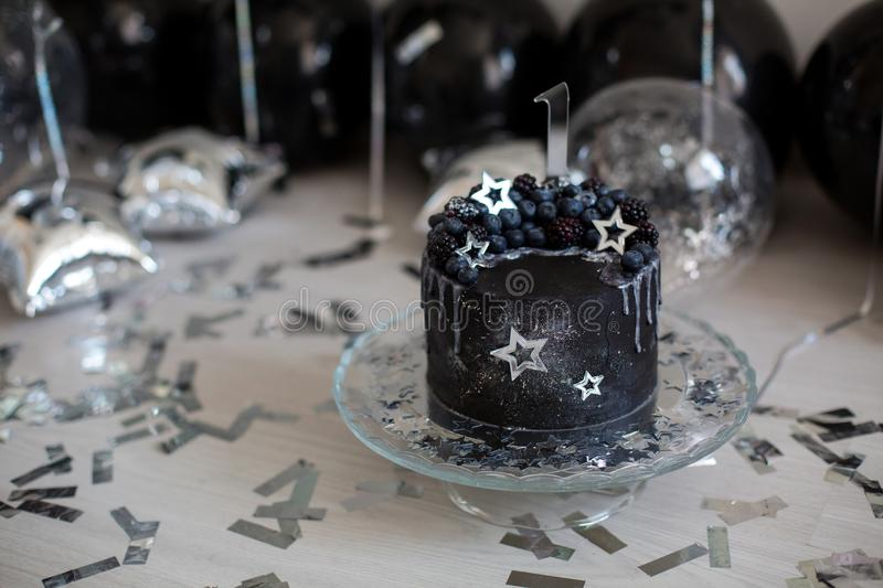Black cake with stars and berries. With the number one stock image