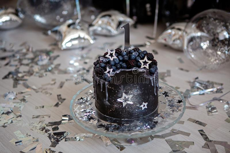 Black cake with stars and berries. With the number one stock photography