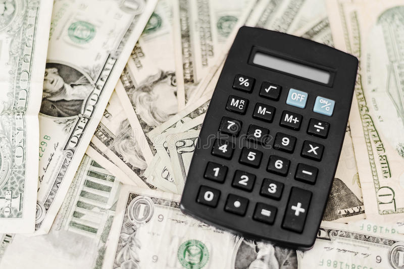 Black calculator on top of dollar bills filling frame. Calculator isolated on various dollar bills, illustrating finance and business concepts stock photos