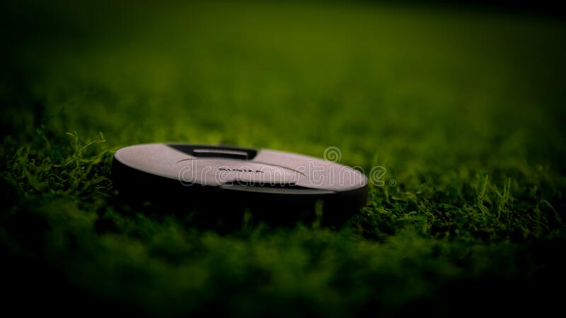 Black Camera Lens Cover on Green Grass royalty free stock images