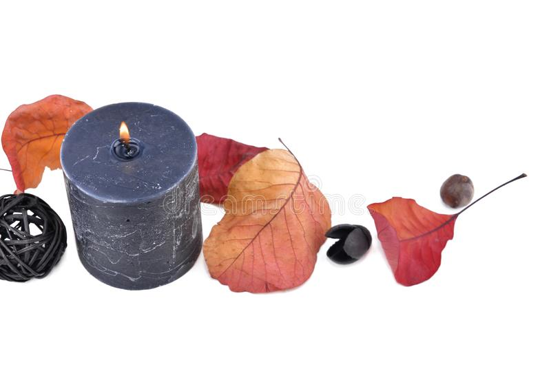 Black candle burning with autumnal leaf royalty free stock images