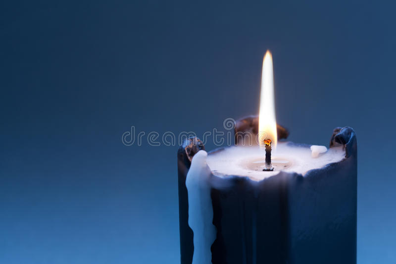 Black candle with burning wick on dark blue gradient background. copy space royalty free stock images