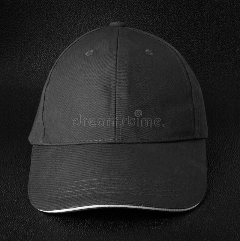 Black cap dark background. Template of baseball cap in front view. Black cap royalty free stock photography