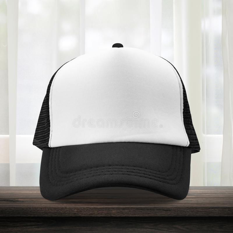 Black cap made from fabric material on dressing room background with mockup baseball caps style. White caps template place on stock image