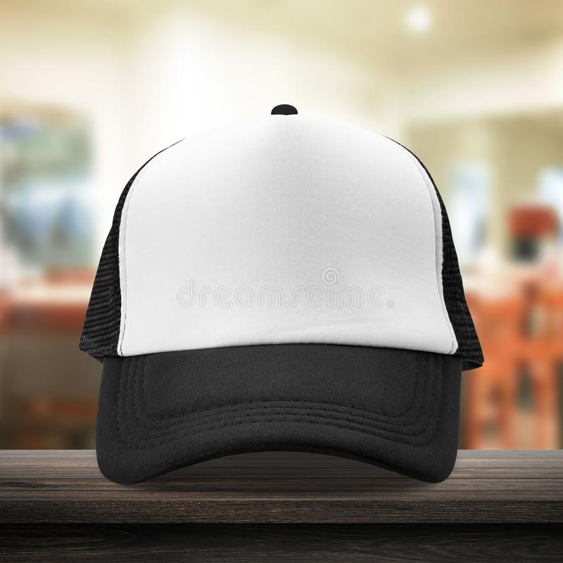 Black cap made from fabric material on dressing room background with mockup baseball caps style. White caps template place on. Wooden table for your design stock photo