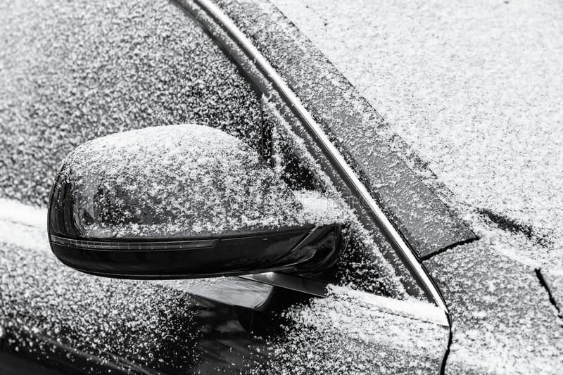 Black car mirror covered with fresh frost stock images
