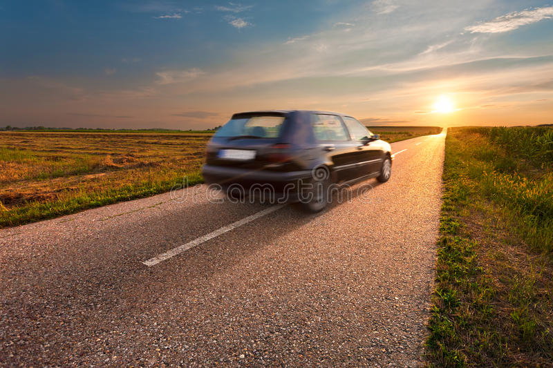 Black car in motion blur on open road. Black car in motion blur on the road towards the setting sun stock photography