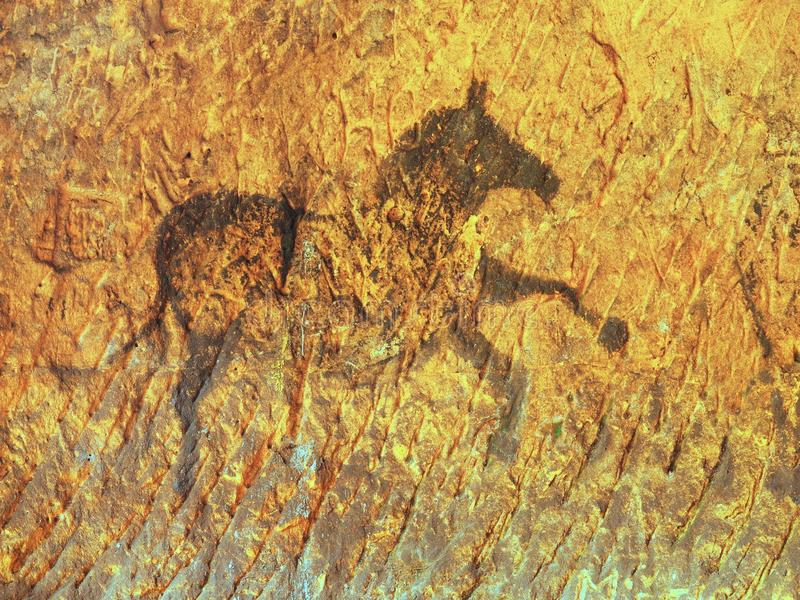 Black carbon paint of horse on sandstone wall. Abstract children art in sandstone cave. Black carbon paint of horse on sandstone wall, copy of prehistoric stock photos