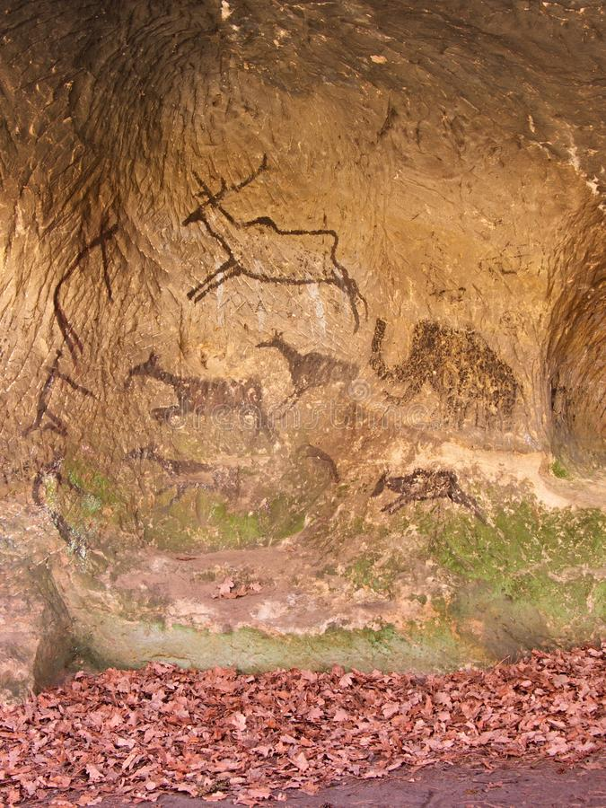 Black carbon paint of human hunting on sandstone wall, copy of prehistoric picture. Abstract children art in cave. Black carbon paint of human hunting on stock photography