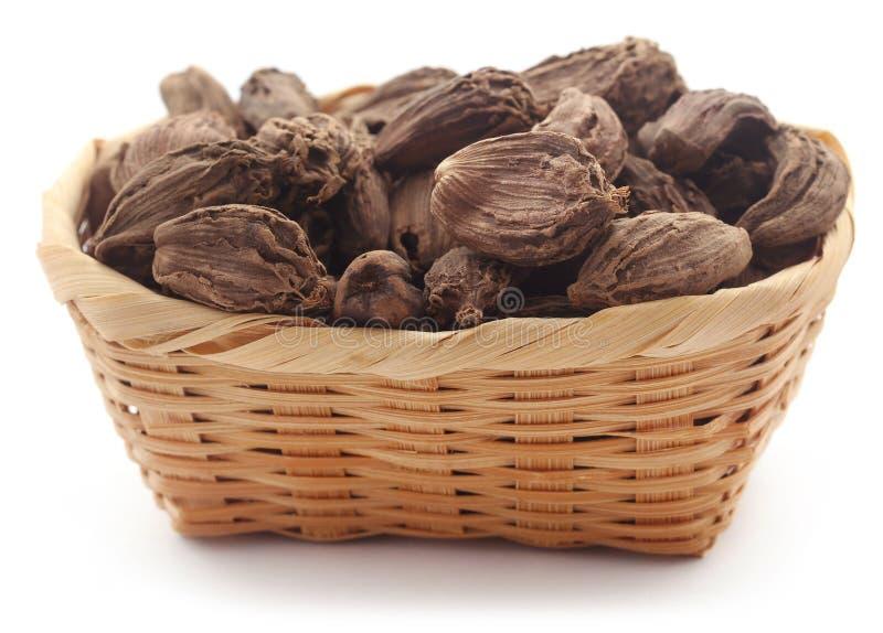 Black cardamom. In a basket over white background stock image