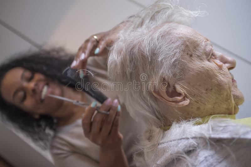 Black girl cuts hair to old white woman stock image