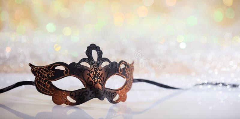 Black carnival mask on bokeh background. Black carnival mask on white surface, abstract bokeh background royalty free stock photo