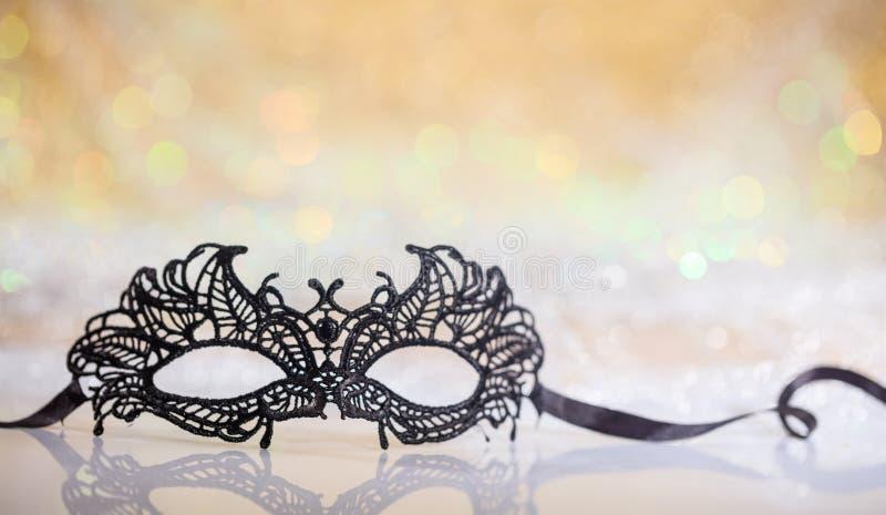 Black carnival mask on bokeh background. Black carnival mask on white surface, abstract bokeh background royalty free stock photography