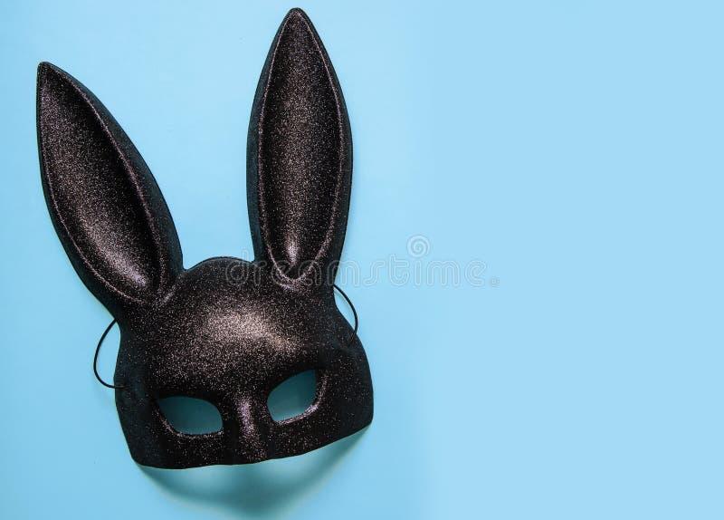 Black mask of rabbit on blue background. Black carnival mask of rabbit on blue background stock photos