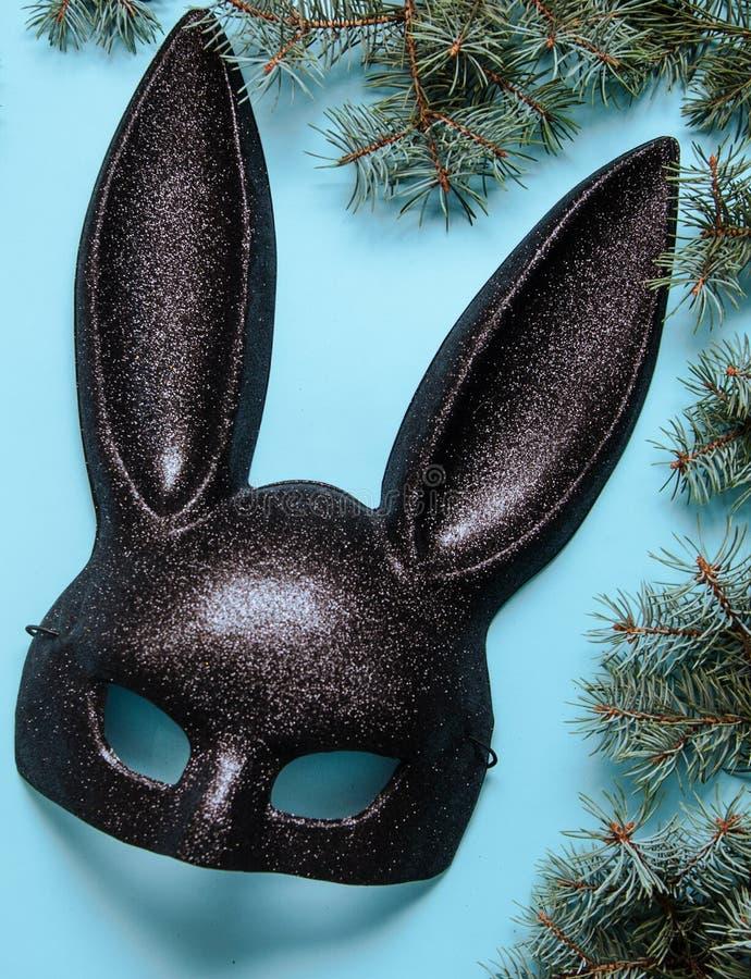 Black mask of rabbit on blue background. Black carnival mask of rabbit on blue background royalty free stock image