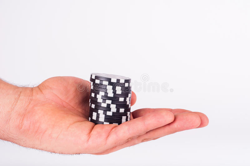 Black casino chips on human hands isolated on white stock photo