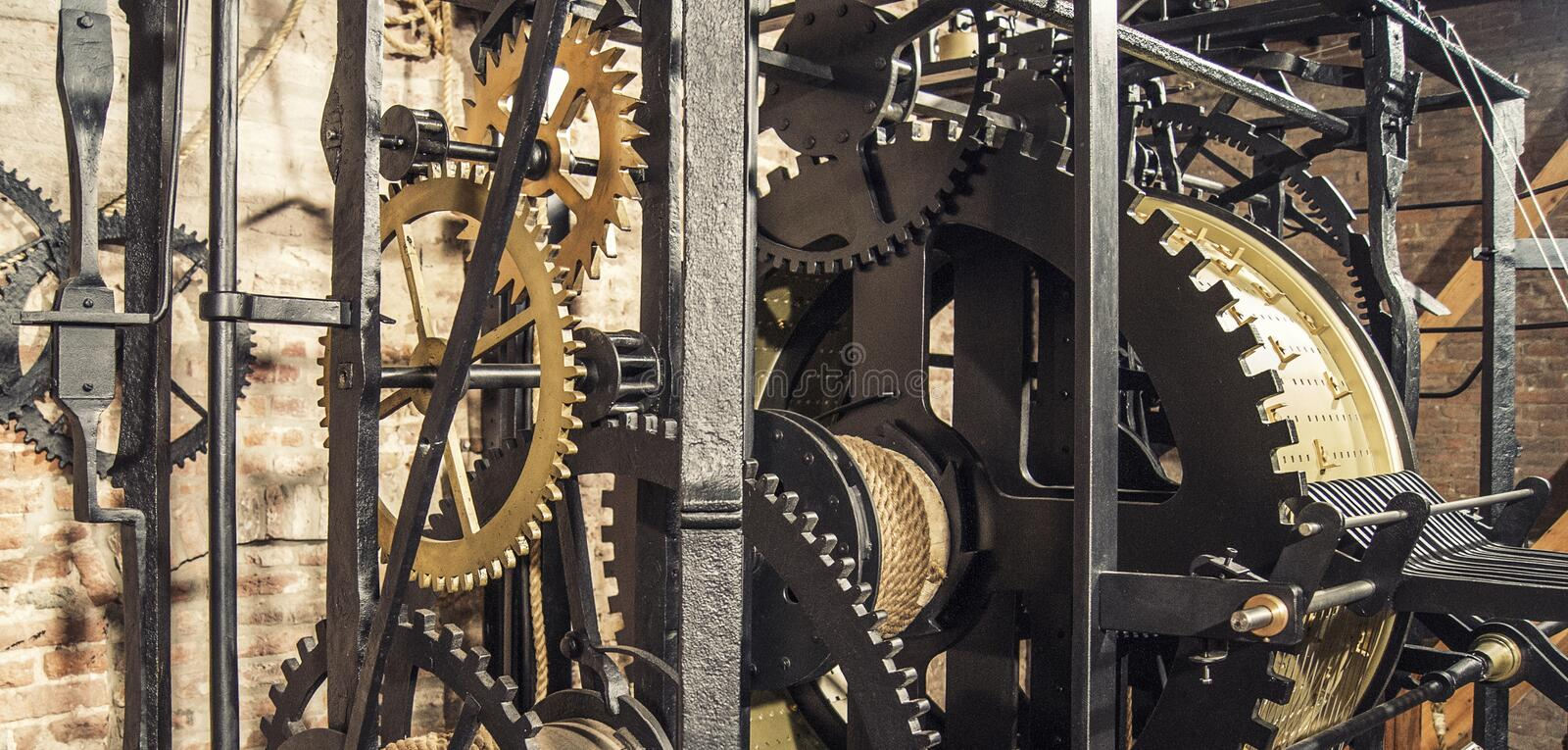 Black cast iron cogwheel. Black and copper colored cast iron cogwheels which are part of a large restored clockwork in a church in the Netherlands stock photo