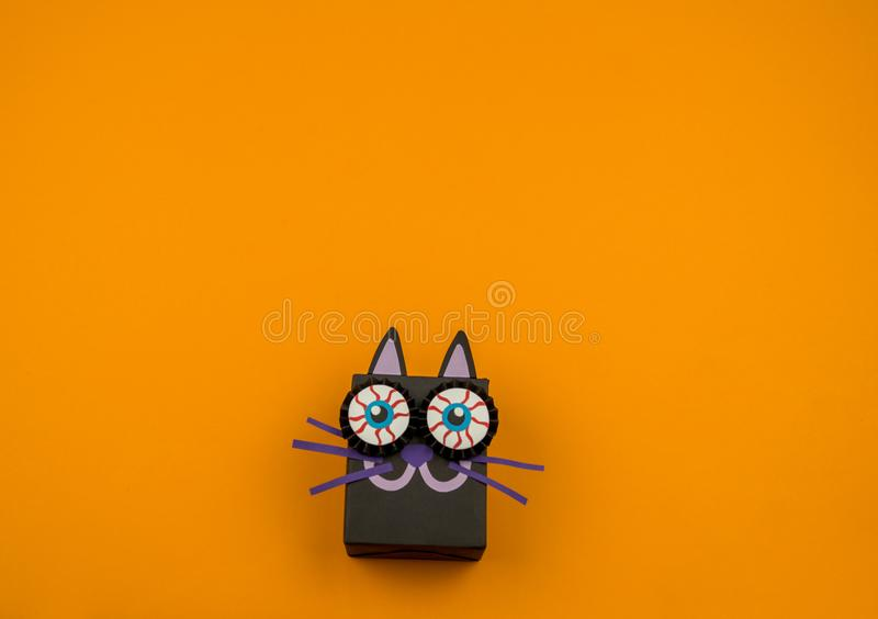 Black cat made of paper on an orange background stock photography