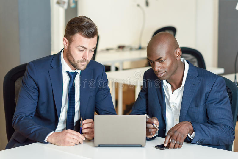 Black and caucasian businessmen looking at a laptop computer. Two men wearing blue suits working in an office with white furniture royalty free stock photography