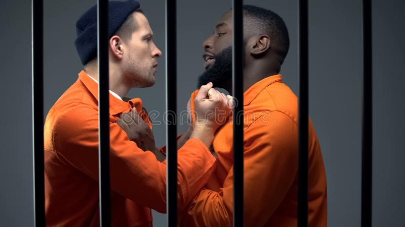 Black and caucasian prisoners having fight in cell, jail overcrowding, conflict royalty free stock photos