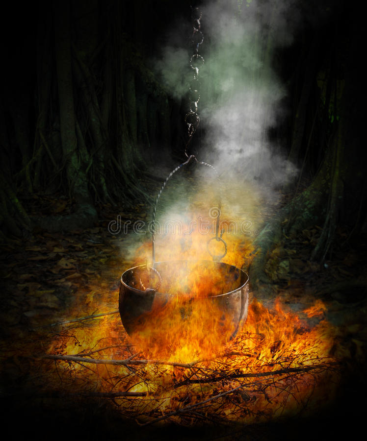 Black cauldron in fire royalty free stock photography