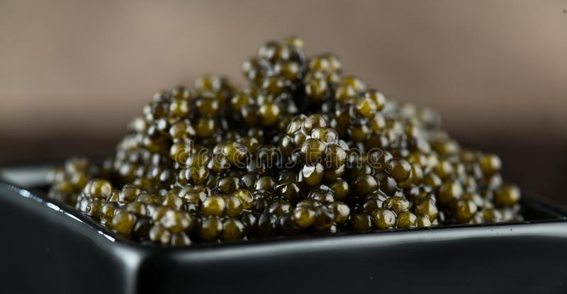 Black Caviar in a bowl. High quality real natural sturgeon black caviar close-up. Delicatessen. Texture of expensive luxury caviar square dish on black stock photo
