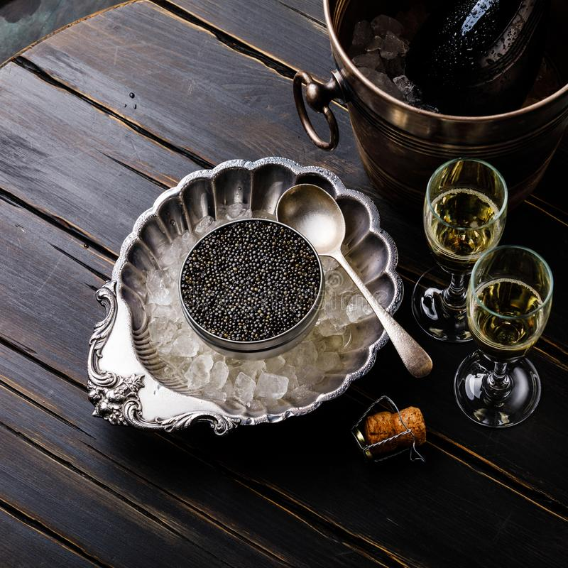 Black caviar in can on ice in silver bowl and champagne stock photos