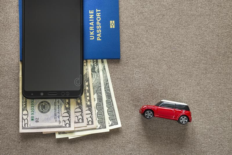 Black cellphone, money American dollars banknotes bills, passport and toy car on copy space background, top view. Travel light,. Comfortable journey vacation royalty free stock photos