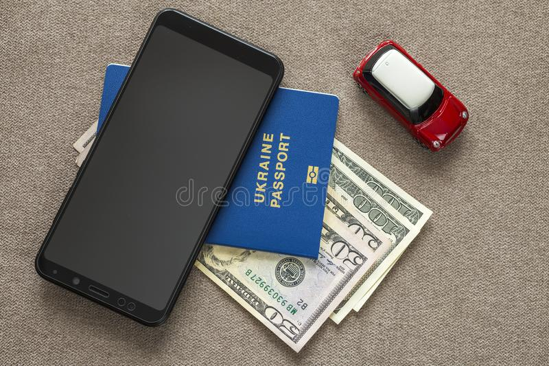 Black cellphone, money American dollars banknotes bills, passport and toy car on copy space background, top view. Travel light,. Comfortable journey vacation stock images