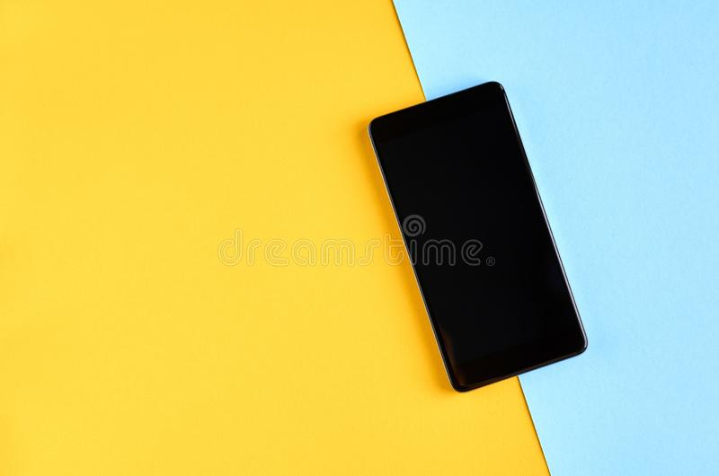 Black cellphone on yellow and blue background composition, mobile phone. Flat lay and top view photo, golden, layout, above, bright, card, concept, copy, space royalty free stock photo
