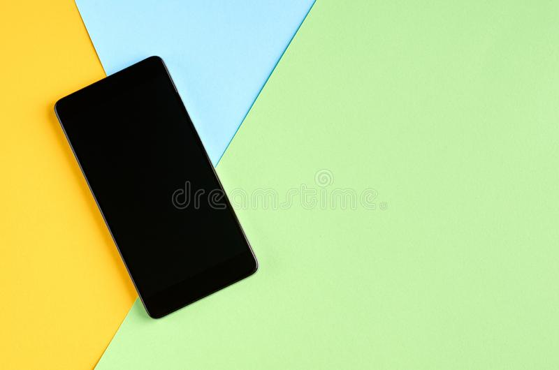 Black cellphone on yellow and blue background composition, mobile phone. Flat lay and top view photo, green, golden, layout, above, bright, card, concept, copy stock images