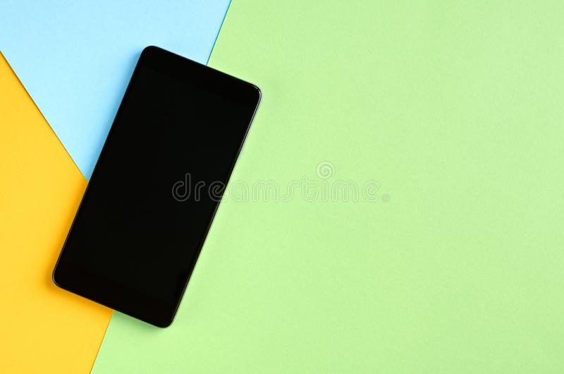 Black cellphone on yellow and blue background composition, mobile phone. Flat lay and top view photo, green, golden, layout, above, bright, card, concept, copy royalty free stock images