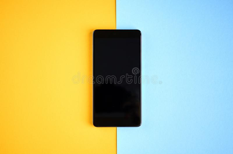 Black cellphone on yellow and blue background composition, mobile phone. Flat lay and top view photo, golden, layout, above, bright, card, concept, copy, space royalty free stock image