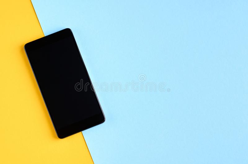 Black cellphone on yellow and blue background composition, mobile phone. Flat lay and top view photo, golden, layout, above, bright, card, concept, copy, space royalty free stock photography