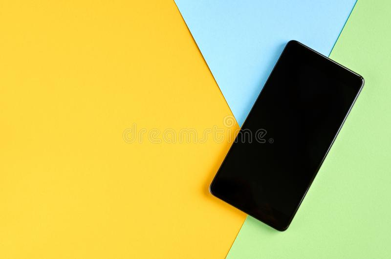 Black cellphone on yellow and blue background composition, mobile phone. Flat lay and top view photo, green, golden, layout, above, bright, card, concept, copy stock photos