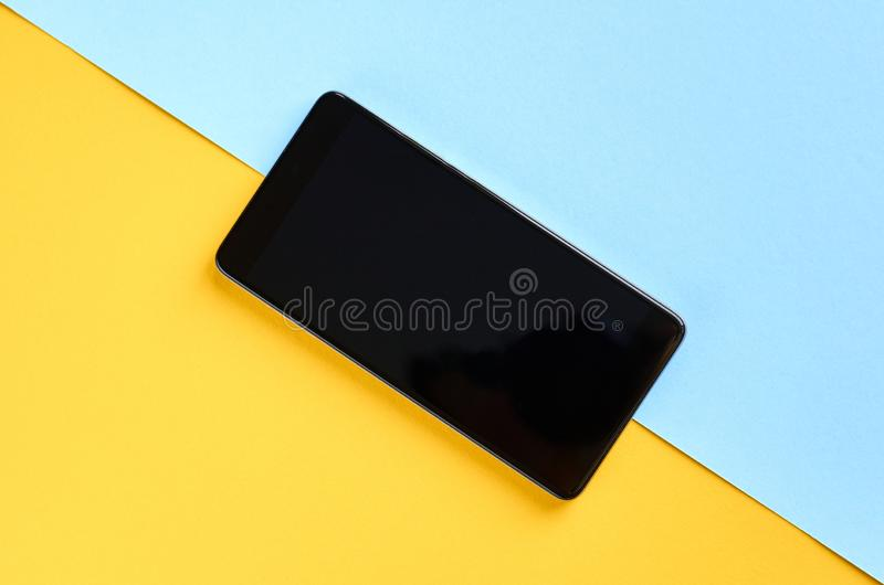 Black cellphone on yellow and blue background composition, mobile phone. Flat lay and top view photo, golden, layout, above, bright, card, concept, copy, space royalty free stock photos