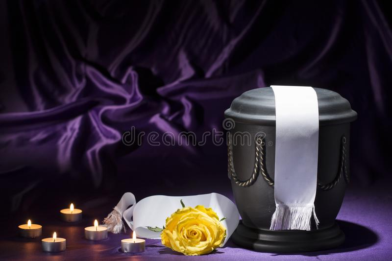 Black cemetery urn with candles yellow rose, and white ribbon on deep purple background stock image