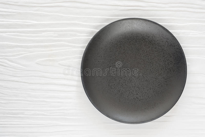 Black ceramic bowl on the white wooden royalty free stock images