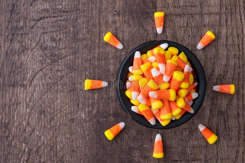 Black ceramic cauldron filled with holiday candy corn on a rustic wood background, with candy corn pointing to bowl stock photo