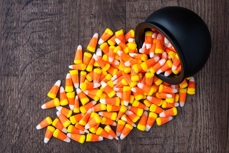 Black ceramic cauldron filled with holiday candy corn tipped over on a rustic wood background, spilling over onto the background stock photography