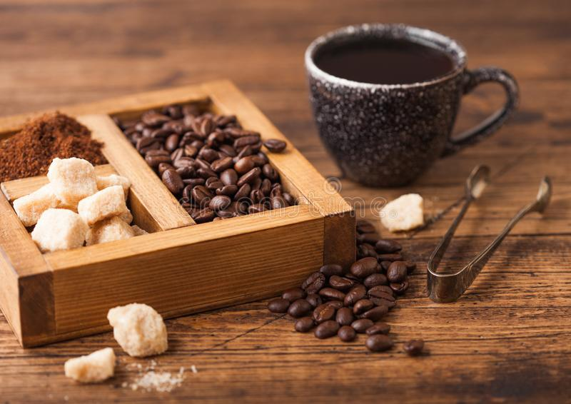Black ceramic cup of fresh raw organic coffee with beans and ground powder with cane sugar in vintage box on wooden background. Black ceramic cup of fresh raw royalty free stock photos