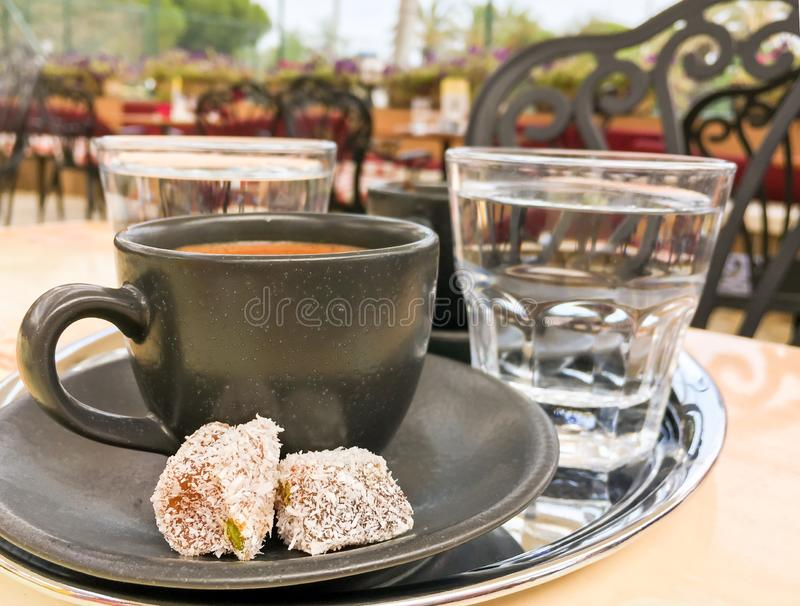 A black ceramic cup of turkish coffee with rahat lokum and glass of water on the tray in summer terrace. Side view stock photos