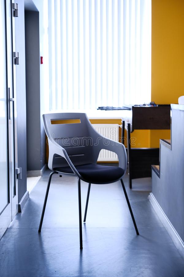 Black chair in corridor of apartment, real photo with copy space on the white wall royalty free stock images