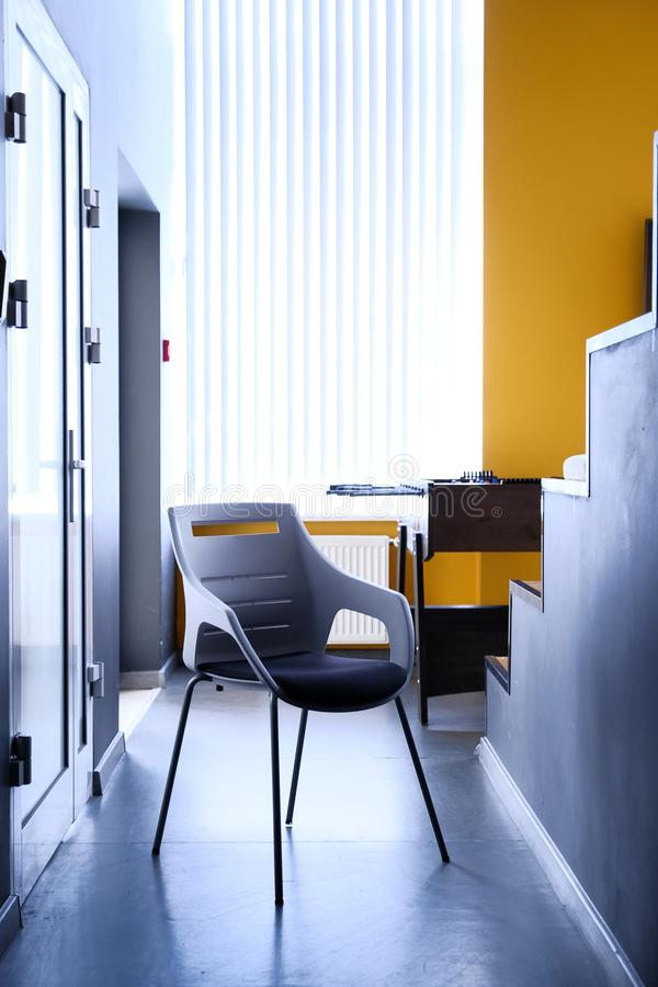 Black chair in corridor of apartment, real photo with copy space on the white wall stock image