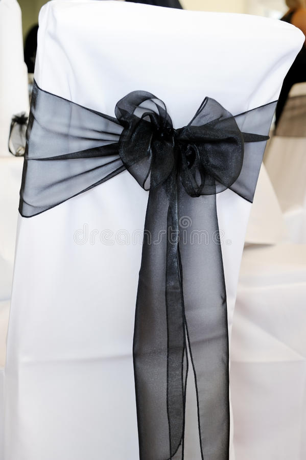 Black chair cover at wedding. White and black chair cover with bow at wedding reception stock photo