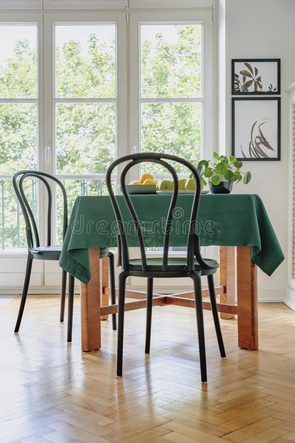 Black chair next to a table with green cloth in a dining room interior. Balcony window in the background. Real photo stock photos
