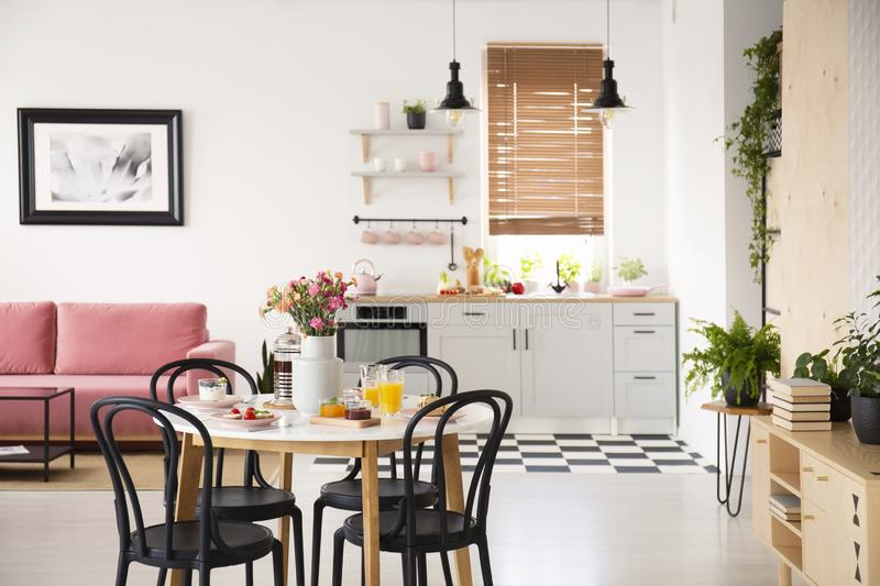 Black chairs at dining table in open space interior with poster above pink sofa and plants. Real photo with blurred background. Concept stock images