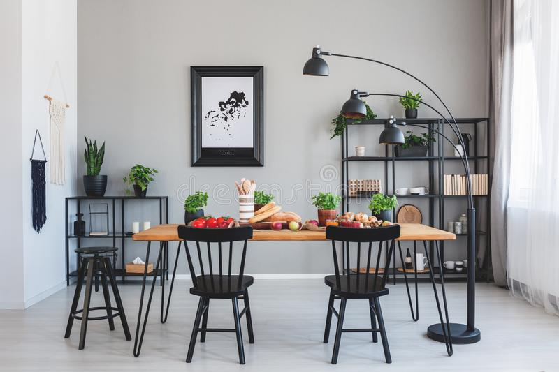 Black chairs at wooden table with food in grey dining room interior with poster and lamp. Real photo royalty free stock image